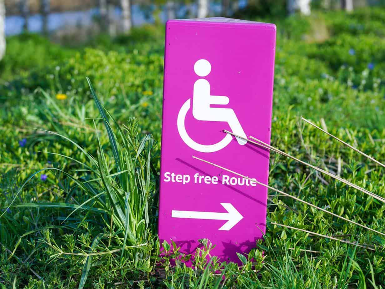 """Grüne Wiese mit einem pinken Schild, auf dem ein Piktogramm einer rollstuhlfahrenden Person und dem Hinweis """"Step Free Route"""""""